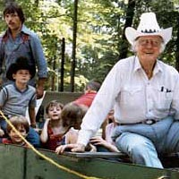 Bill Monroe taking children for a ride in his mule-drawn farm wagon, 1984