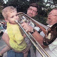 "Child ""tries out"" trombone of Lawrence City Band member, July 1999"