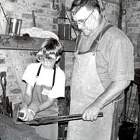 Karl Nettles teaches blacksmithing to a young girl