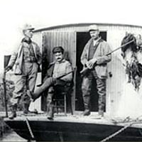 Capt. J.W. Quillen on his shantyboat with two hunters, c. 1920
