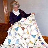 "Teresa McGuigan Hentosz with hand-pieced quilt ""Sparkling Gems,"" made in 1998 from old feed bags"