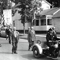 Parade, ca. 1955 - Motorcycle policeman leads men carrying their banner