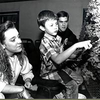 Two students show young boy technique for decorating a parade float, 1989.