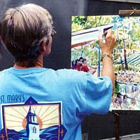 Artist Sue Hand painting a scene from the St. Mary's Homecoming Picnic