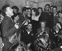 Pete Seeger singing to an audience that includes whites and African Americans.