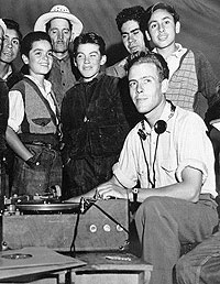 Charles L. Todd with recording equipment as boys and men look on.