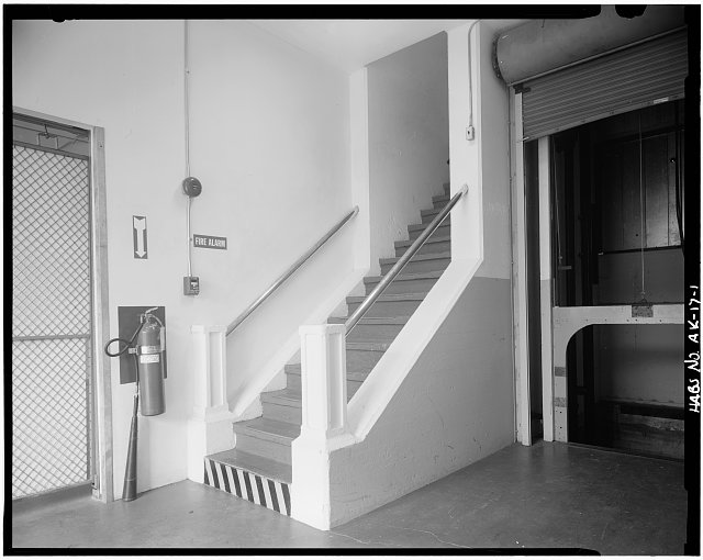 1.  INTERIOR VIEW SHOWING THE ORIGINAL STAIRWAY. BOTTOM OF STAIRS FACE THE DOCK AREA. THE ELEVATOR ON THE RIGHT DOES NOT APPEAR TO BE ORIGINAL. - U. S. Coast Guard Headquarters Building, Ketchikan, Ketchikan Gateway Borough, AK