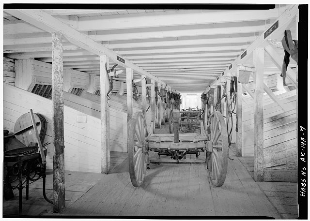 7.  INTERIOR, GROUND FLOOR, LOOKING WEST SHOWING WAGON - Fort Egbert, Mule Barn, Yukon River at Mission Creek, Eagle, Southeast Fairbanks Census Area, AK