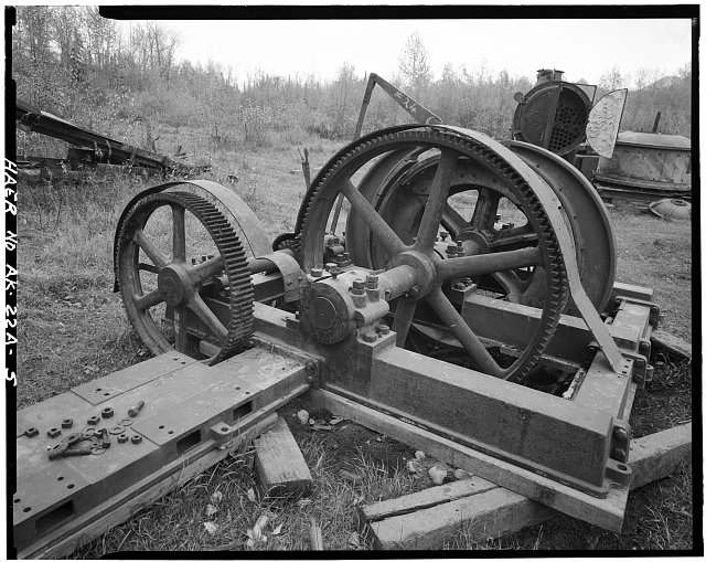 5.  OBLIQUE VIEW OF HOIST, SHOWING REDUCTION GEARS AND BED FOR (MISSING) CLUTCH/DRIVE GEAR UNIT, LOOKING EAST (McNALLY DRYER AND COVER SHOWN IN EXTREME UPPER RIGHT BACKGROUND) - Buffalo Coal Mine, Vulcan Cable Hoist, Wishbone Hill, Southeast end, near Moose Creek, Sutton, Matanuska-Susitna Borough, AK