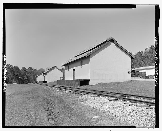 Oblique view of rear and south sides of ammunition storage buildings 4403 and 4404, view towards the north without scale - Fort McClellan Ammunition Storage Area, Building No. 4403, Second Avenue (Magazine Road), Anniston, Calhoun County, AL