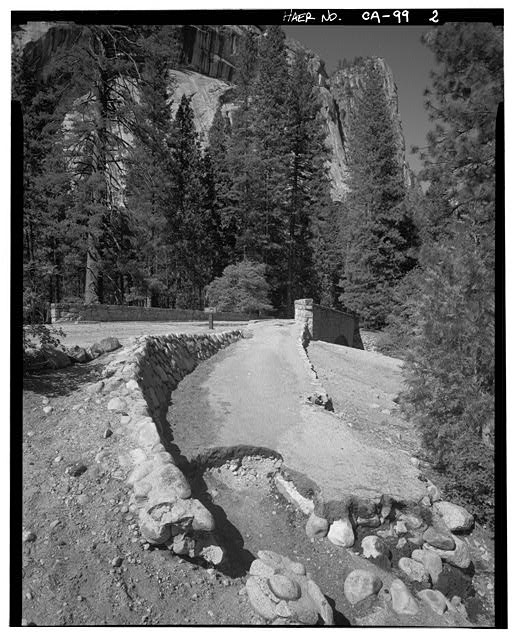 2.  FACING EAST AT SW CORNER, RETAINING WALL, ERODED FOOTPATH APPROACH AND WASHINGTON'S COLUMN IN THE DISTANCE. - Sugar Pine Bridge, Spanning Merced River on service road, Yosemite Village, Mariposa County, CA