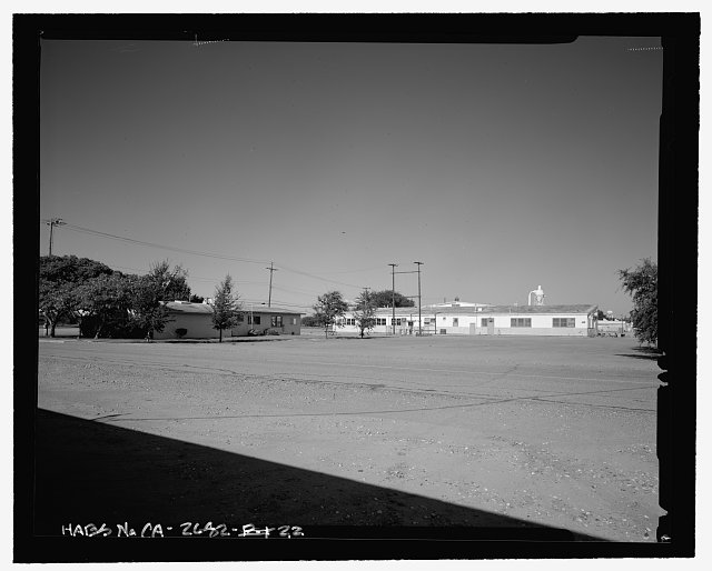 Contextual view of south end of Hooper Drive.  Bachelor officer's quarters (building no. 24) is shown in background.  Camera facing northeast. - Naval Supply Annex Stockton, Rough & Ready Island, Stockton, San Joaquin County, CA