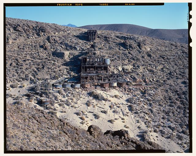 40.  NORTH ELEVATION OF SKIDOO MILL, LOOKING SOUTH. TAILINGS IN FOREGOUND, DOWN SLOPE FROM CYANIDE PROCESSING TANKS. SEE CA-290-5 FOR IDENTICAL B&W NEGATIVE. - Skidoo Mine, Park Route 38 (Skidoo Road), Death Valley Junction, Inyo County, CA
