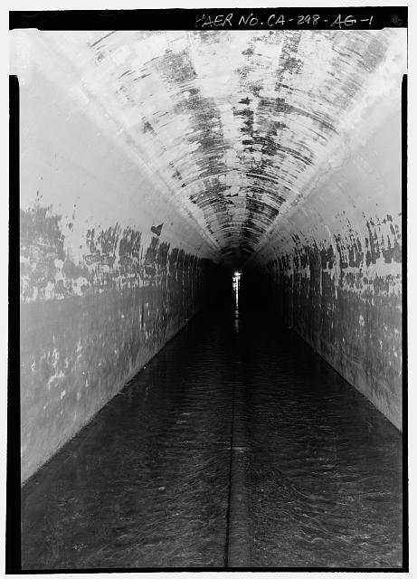 INTERIOR TUNNEL, CITY LIMITS. STATION 767+00 FEET. LOCATION IS 1/2 WAY BETWEEN ELLESMERE AND THE CASCADES. LIGHT IN DISTANCE PROVIDED BY INSPECTION WORKERS WALKING TOWARD CAMERA - Los Angeles Aqueduct, Tunnel Interior, Los Angeles, Los Angeles County, CA