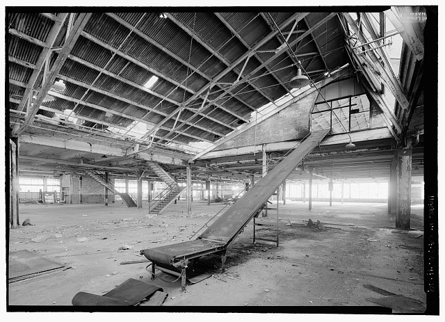 19.  VIEW TO SOUTHWEST OF FIRST FLOOR SHOWING CONVEYOR FOR MOVING MATERIAL TO SECOND FLOOR. (NOTE: THIS IS NOT AN ORIGINAL CONVEYOR FOR MOVING BODY PARTS) STAIRS IN BACKGROUND LEAD TO SECOND FLOOR VIA TOILET ROOM NO. 4 AND COAT ROOM AT MEZZANINES LEVEL SITUATED BETWEEN THE TWO SETS OF STAIRS. THERE ARE THREE OTHER TOILET/COAT ROOM MEZZANINES TO THE NORTH LOCATED ALONG THE WALL BETWEEN THE FIRST AND SECOND FLOORS, BEHIND AND TO THE LEFT OF THE STAIRS IS A FREIGHT ELEVATOR SHAFT. - Rosie the Riveter National Historical Park, Ford Assembly Plant, 1400 Harbour Way South, Richmond, Contra Costa County, CA