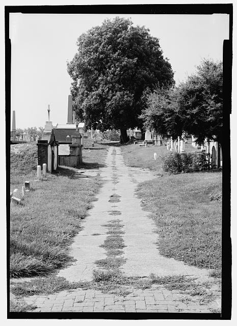 VIEW LOOKING SOUTH ALONG COOMBE AVENUE (FORMER CEREMONIAL ENTRANCE). NOTE PUBLIC VAULT AT RIGHT EDGE OF VIEW AND TYPICAL MID-NINETEENTH CENTURY MAUSOLEUMS AT LEFT.   - Congressional Cemetery, 1801 E Street, Southeast, Washington, District of Columbia, DC
