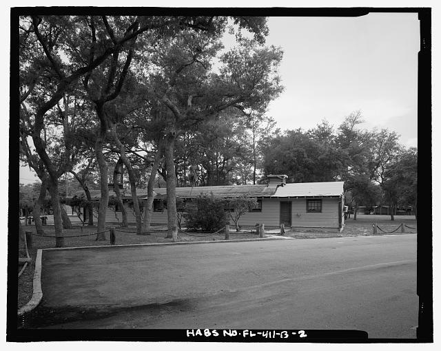 OBLIQUE VIEW OF WEST (FRONT) FACADE, LOOKING EAST/NORTHEAST - Eglin Air Force Base, Storehouse & Company Administration, Southeast of Flager Road, Nassau Lane, & southern edge of Weekly Bayou, Valparaiso, Okaloosa County, FL