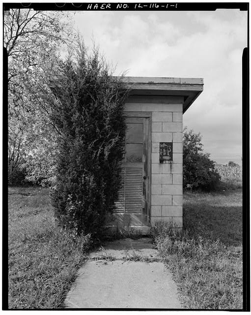 1.  SHED. SOUTH END OF SHORTER BARRACKS, FRONT, LOOKING WEST. - NIKE Missile Base C-84, Paint & Oil Storage Shed, South of Launch Area Entrance Drive, near security fence, Barrington, Cook County, IL