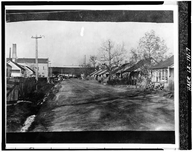7.  Photocopy of c. 1906 photograph looking NE along Main Street towards mill complex showing workers' housing on both sides of street, - Laurel Valley Sugar Plantation, Double Creole Quarters, 2 Miles South of Thibodaux on State Route 308, Thibodaux, Lafourche Parish, LA