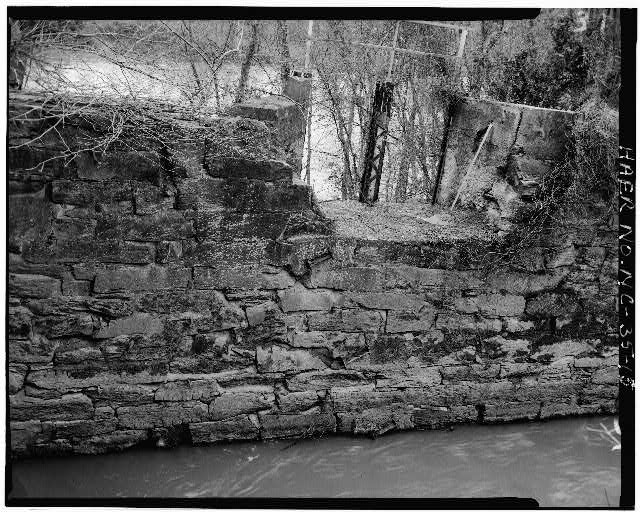 13.  VIEW OF MASONRY RETAINING WALLS ON SOUTH SIDE OF CANAL AT POWERHOUSE - Lockville Hydroelectric Plant, Deep River, 3.5 miles upstream from Haw River, Moncure, Chatham County, NC