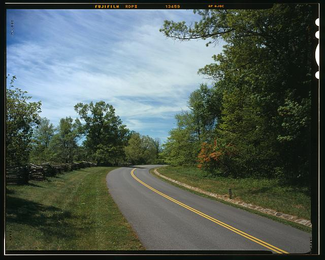 248.  Smart view Recreation Area. View of one of the parkway curves with a snake fence on the left and a stone drain on the right reinforcing the roadway alignment. Looking north-northeast. - Blue Ridge Parkway, Between Shenandoah National Park & Great Smoky Mountains, Asheville, Buncombe County, NC