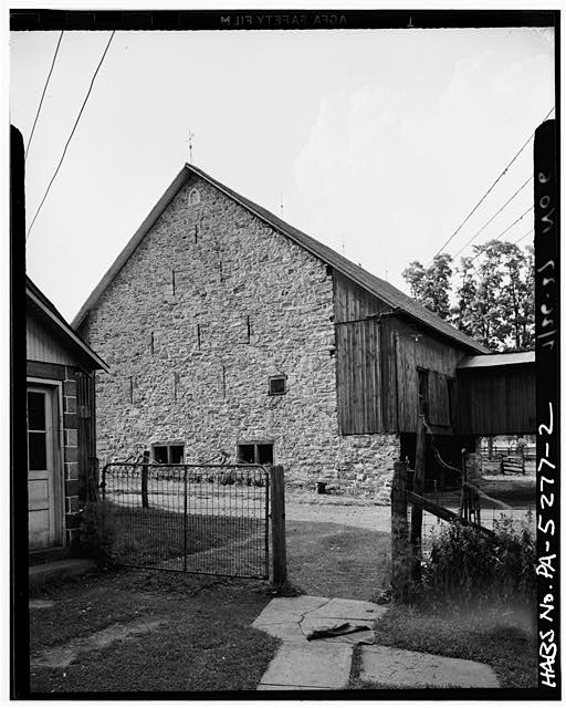 2.  SIDE VIEW. NOTE BRIDGE ON OVERHANG. DATE STONE READS A & S LEE 1797. ALSO NOTE SLIT VENTILATORS. - A. & S. Lee Barn (1797), Between State Route 73 & Manatawny Creek, Boyertown, Berks County, PA