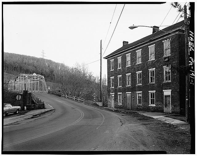 1.  GENERAL VIEW IN FREEMANSBURG, BRIDGE IN LEFT BACKROUND AND Q.U.A.M. HALL (BRIDGE COMPANY BUILDING) IN FOREGOUND. - Freemansburg-Steel City Bridge, Spanning Lehigh River between Freemansburg & Steel City, Freemansburg, Northampton County, PA