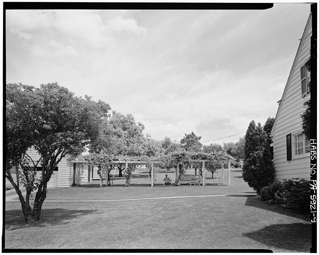 9.  VIEW OF MARY WOLK IN HER ARBOR, NEXT TO GARAGE AND HOUSE, EAST LAUREL CIRCLE AT LILAC DRIVE, SECTION B - Town of Norvelt, Norvelt, Westmoreland County, PA