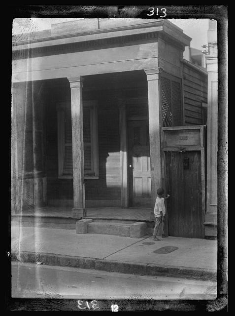 Boy standing on a sidewalk by a doorway, New Orleans or Charleston, South Carolina