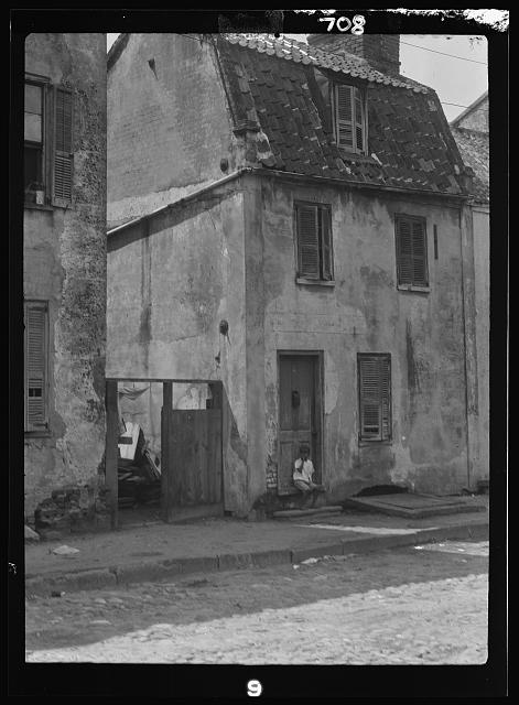 Boy sitting in the doorway of a two-story building, New Orleans or Charleston, South Carolina