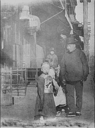Man and children walking down a street, Chinatown, San Francisco