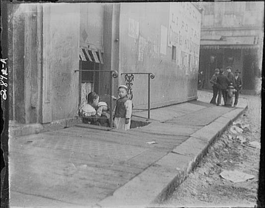 Three children in front of a cellar door, Chinatown, San Francisco