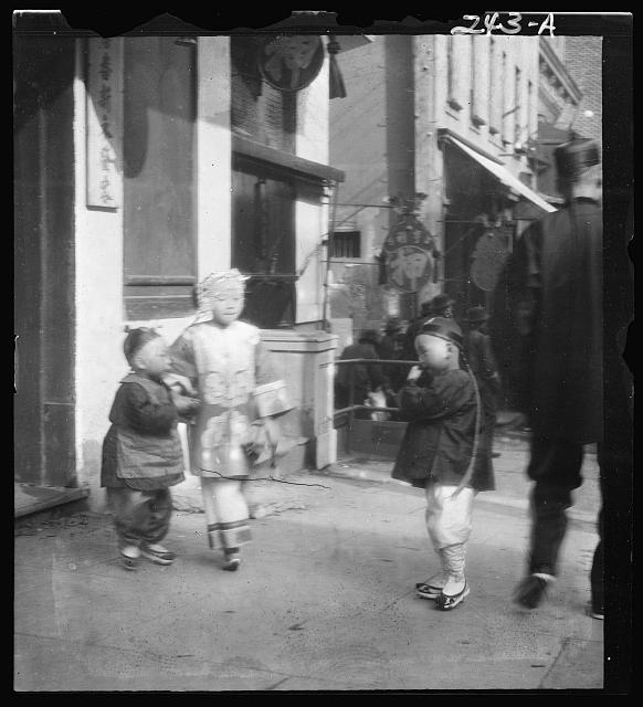 Three children standing on a sidewalk, Chinatown, San Francisco