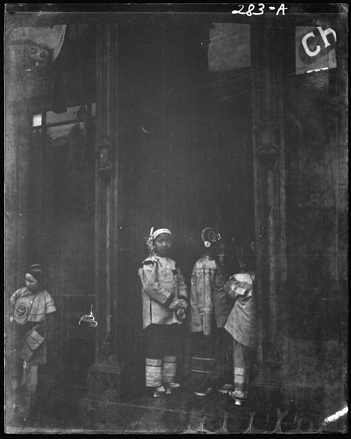 Three girls standing in a doorway, Chinatown, San Francisco