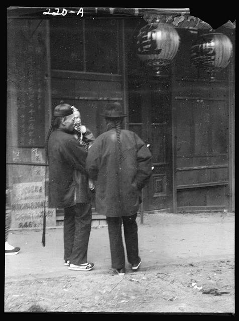 Two men, one holding a child, standing in the street, Chinatown, San Francisco