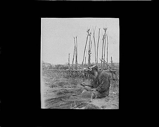 Ainu man seated outside working on nets