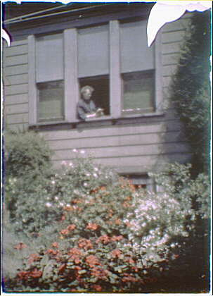 Arnold Genthe dressed in a kimono reading by the window of his house in San Francisco