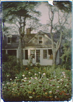 House with a person seated outside at an easel and two people at a window
