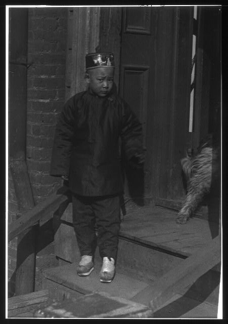 Boy standing on steps in front of a doorway, Chinatown, San Francisco