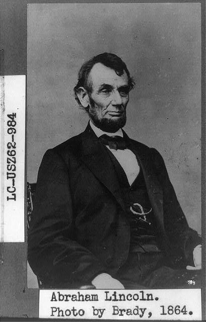 [Abraham Lincoln, three-quarter length portrait, seated, facing right; hair parted on Lincoln&#39;s right side]