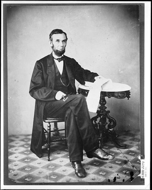[Abraham Lincoln, seated next to a table]
