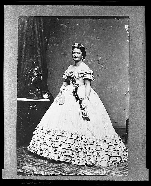[Mrs. Abraham Lincoln, full-length portrait, standing, facing left, near table]