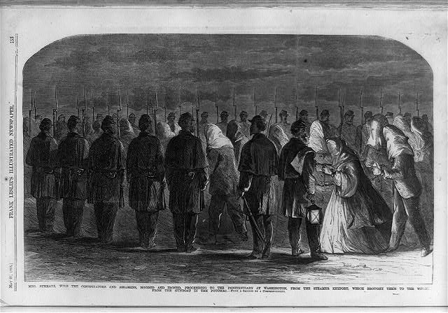 Mrs. Surratt with the conspirators and assassins, hooded and ironed proceeding to the penitentiary at Washington, from the steamer Keyport which brought them to the wharf from the gunboat in the Potomac