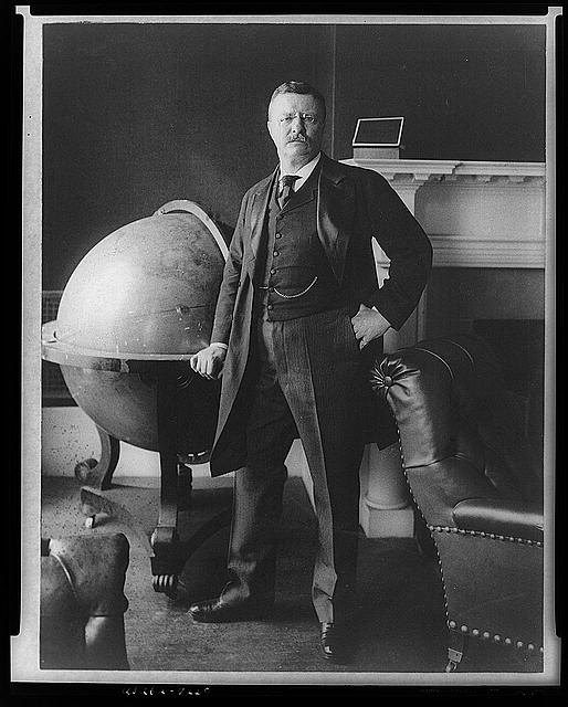 [Theodore Roosevelt, full-length portrait, standing beside large globe, facing front]