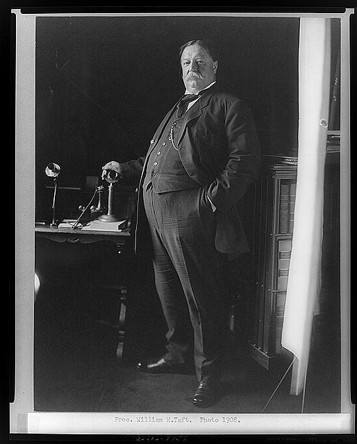 [William H. Taft, full-length portrait, standing, facing left, with hand on telephone]