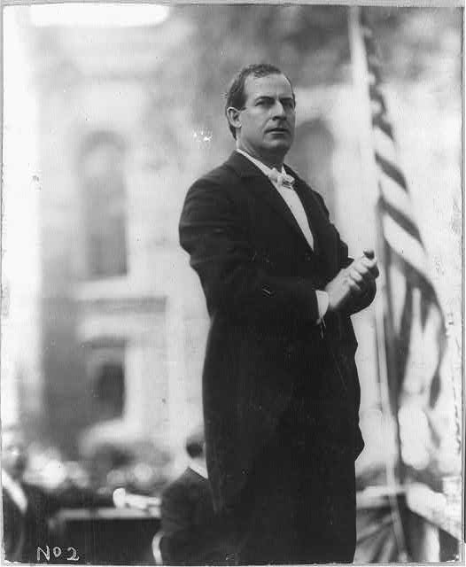 [William Jennings Bryan, Democratic party presidential candidate, three-quarter length view standing on stage next to American flag]