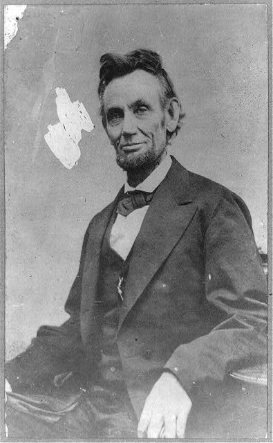 [Abraham Lincoln, half-length, seated, facing front, with hand on arm of chair]