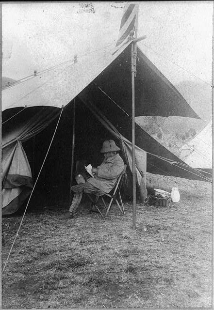 Roosevelt reading in front of his tent in hunting camp
