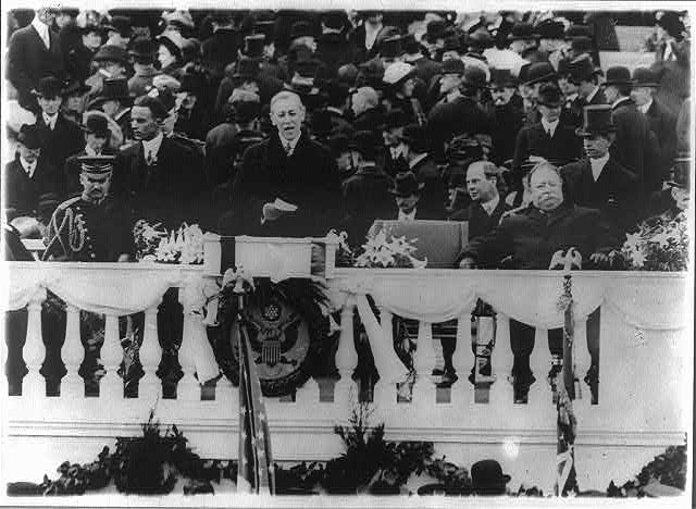 [Woodrow Wilson speaking at his first inauguration on the east portico of the U.S. Capitol, March 4, 1913, with the Great Seal of the United States hanging below him]