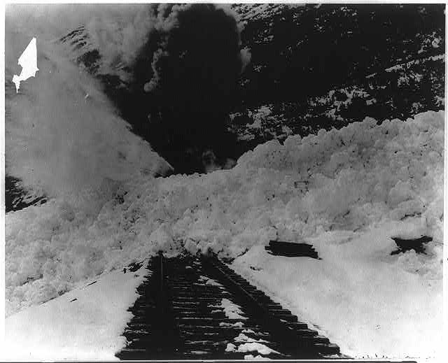Alaska. Rotary snow plow boring through snow bank to clear way for supply train